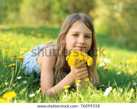 Girl wit a dandelions bouquet on green meadow - stock photo