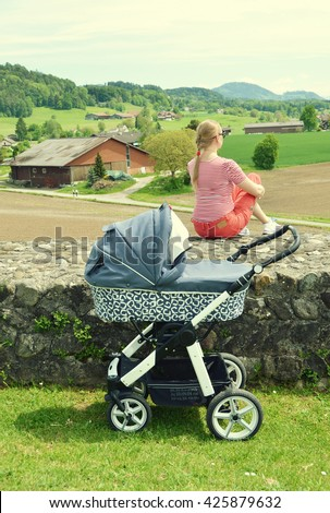 Girl with a baby stroller enjoying Alpine panorama. Switzerland - stock photo