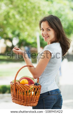 Girl with a basket of fruit and vegetables