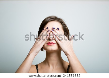 girl with a beautiful face closed her eyes for a surprise, a photo studio on isolated gray background - stock photo