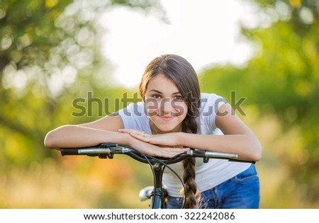 Girl with a bicycle in a summer park - stock photo