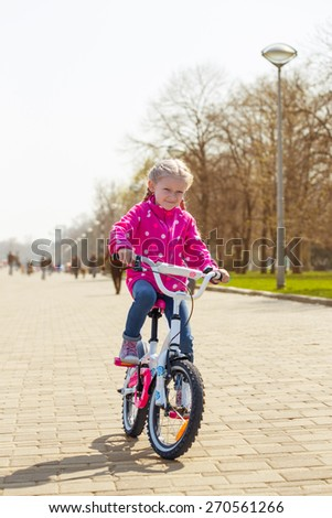 Girl with a bicycle on a walk in the park  - stock photo