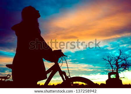 Girl with a bicycle watching the sunset - stock photo