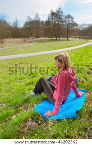 Girl with a big backpack sitting on grass - stock photo