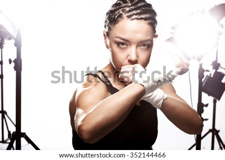 girl with a boxing pose in a studio - stock photo