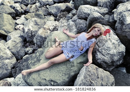 Girl with a broken and a broken head is on the rocks - stock photo