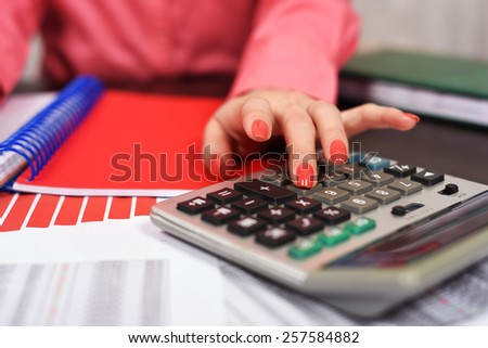 girl with a calculator considers the household budget - stock photo