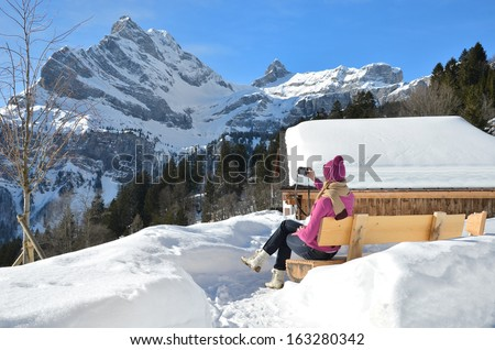Girl with a camera in Swiss Alps  - stock photo