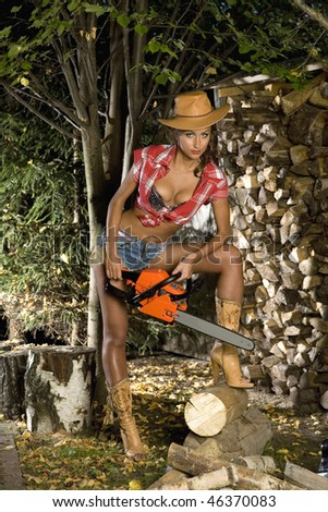 Girl with a chainsaw in the autumn garden - stock photo