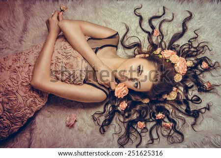 girl with a circlet of flowers on head. charming girl with a flowers. young woman has a beautiful face. girl lying on fur with her long hair - stock photo