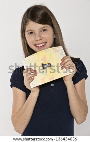 Girl with a copybook with a cat on the cover - stock photo