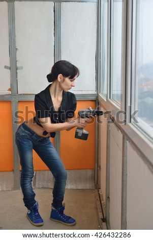 Girl with a drill secures insulation on the balcony