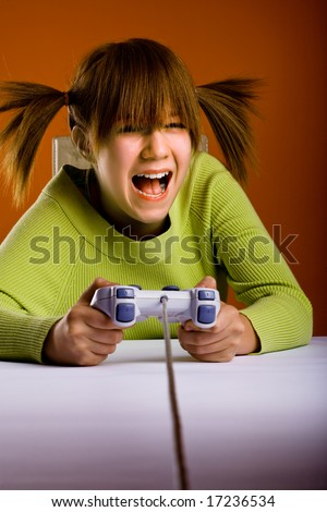 girl with a game controller playing a computer game - stock photo