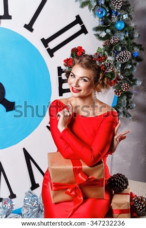 Girl with a gift and a hair sitting next to a large clock. Five to midnight. Christmas Eve. New Year. Waiting for a miracle. Merry Christmas. - stock photo