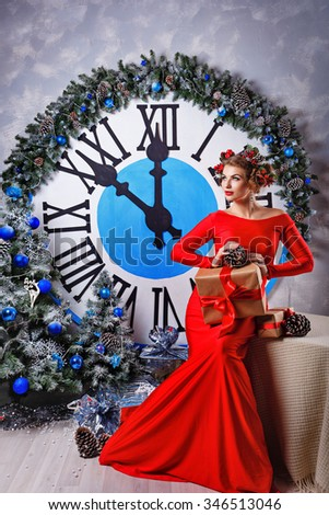 Girl with a gift and hairstyle sitting beside a large clock and a Christmas tree. Christmas Eve. New Year. Waiting for a miracle. Merry Christmas. 2017 - stock photo