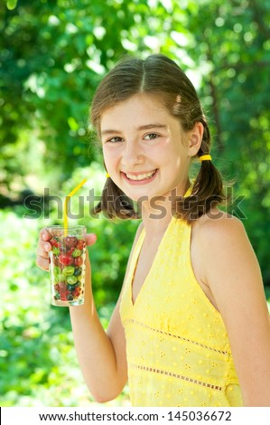 Girl with a glass of fresh berries and fruits. Drinking juice