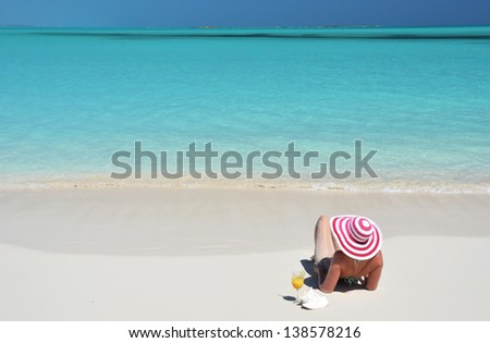 Girl with a glass of orange juice on the beach of Exuma, Bahamas - stock photo