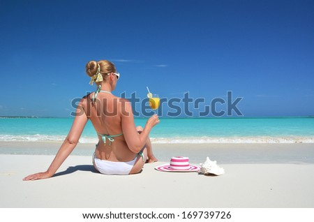 Girl with a glass of orange on the beach of Exuma, Bahamas  - stock photo