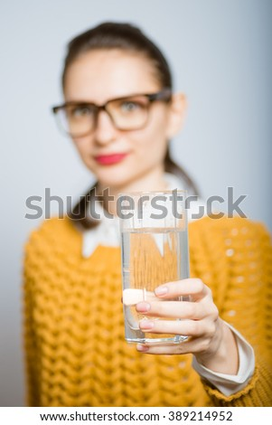 Girl with a glass of water, hipster glasses isolated on a gray background - stock photo