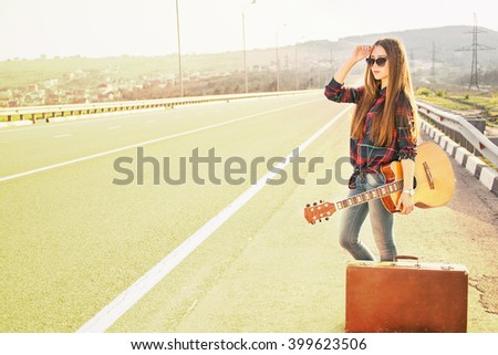 Girl with a guitar on the road vote. Image with sunlight effect. - stock photo