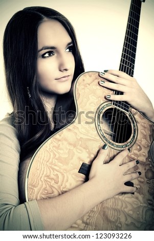 girl with a guitar sitting on a white floor , isolated - stock photo