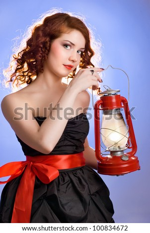 Girl with a kerosene lamp on a blue background - stock photo
