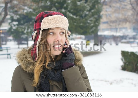girl with a lumberjack hat talking on her cellphone in the snow