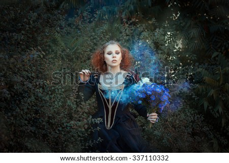 Girl with a magic wand.  Red-haired girl in the forest enchants a bouquet of flowers. - stock photo