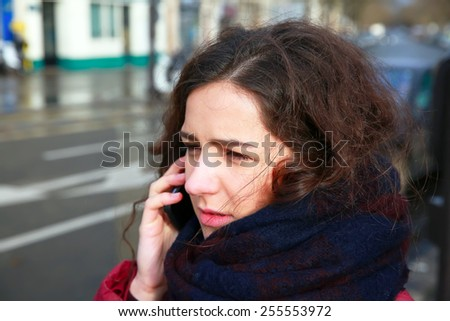 Girl with a mobile phone speaking outside.