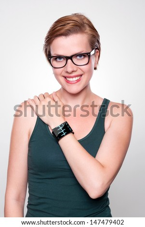 Girl with a modern Internet Smart Watch on grey background. On the screen you can see an EKG Heartbeat Frequenz. All Texts, Icons, Interfaces of the Smart Watch where created from scratch by myself. - stock photo