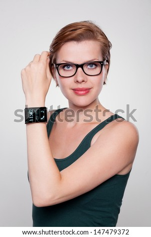 Girl with a modern Internet Smart Watch on grey background. On the screen you can see the lockscreen. All Texts, Icons, Computer Interfaces of the Smart Watch where created from scratch by myself. - stock photo