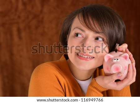 girl with a piggy bank on a brown background - stock photo