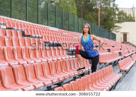 Girl with a pink bottle is at the stadium. - stock photo