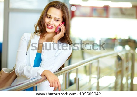 Girl with a pleasant smile speaking over the phone indoors