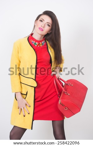 girl with a red bag and dress in a yellow coat - stock photo