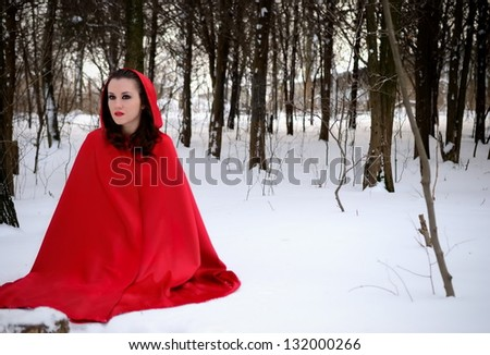 Girl with a red cloak sitting in the snow - stock photo