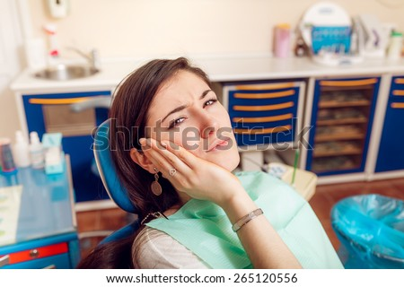 girl with a sick tooth at the dentist - stock photo