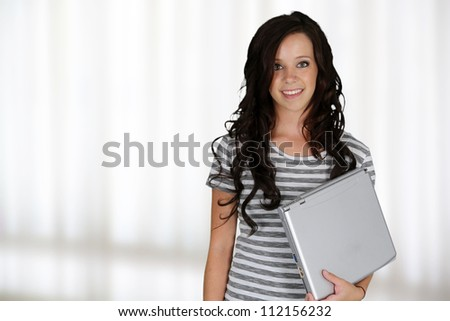 Girl with a stack of books at her school - stock photo