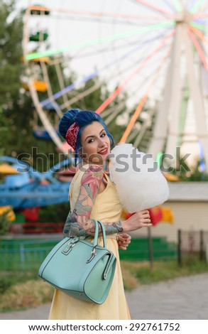 Girl with a tattoo with cotton candy in the hands of an amusement park on the background of traits kolesa.Retro style. - stock photo