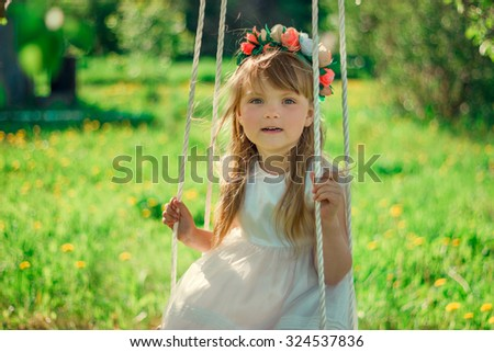 girl with a wreath on his head on a swing smiling - stock photo