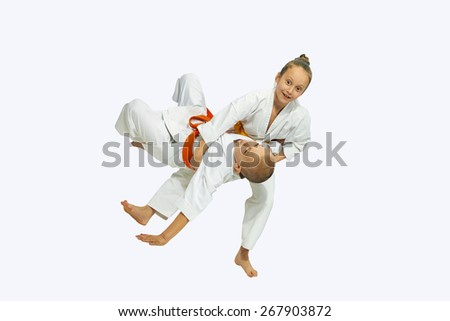 Girl with a yellow belt throws through the thigh of a boy  - stock photo