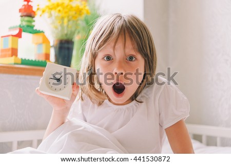 Girl with alarm clock. little girl holding alarm clock. girl in bed looking at the alarm clock. time to wake up.