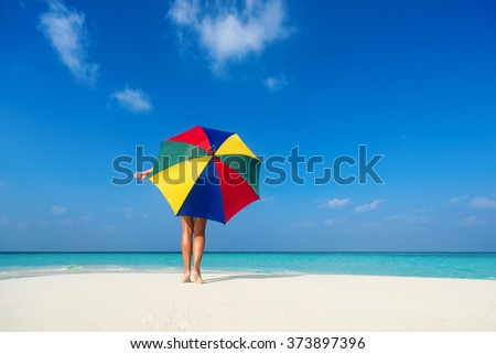 Girl with an colorful  umbrella on the sandy beach - stock photo