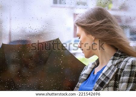 Girl with an umbrella in the rain - stock photo