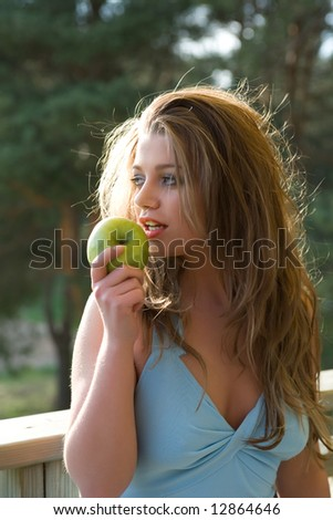Girl with apple on sunset on green background