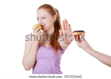 Girl with apple refusing cookie on isolated white background