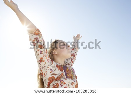Girl with arms outstretched against a blue sky with the sun filtering through her arm. - stock photo
