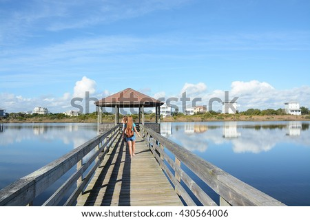 Girl  with backpack hiking on her vacation. Friends walking on the pier, houses in the background, North Topsail Beach, North Carolina. - stock photo