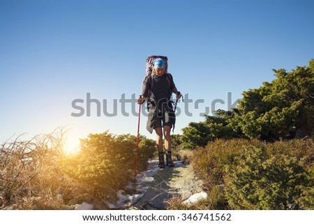 Girl with backpack is traveling in the mountains.