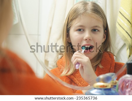 Girl with bathrobe brushing her teeth